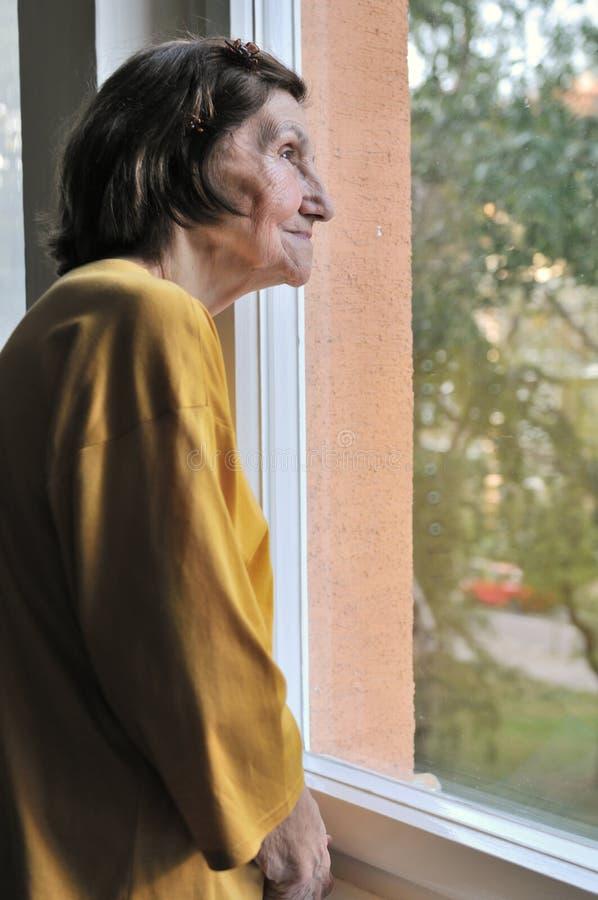 sembrare la donna maggiore della finestra di solitudine fotografie stock libere da diritti