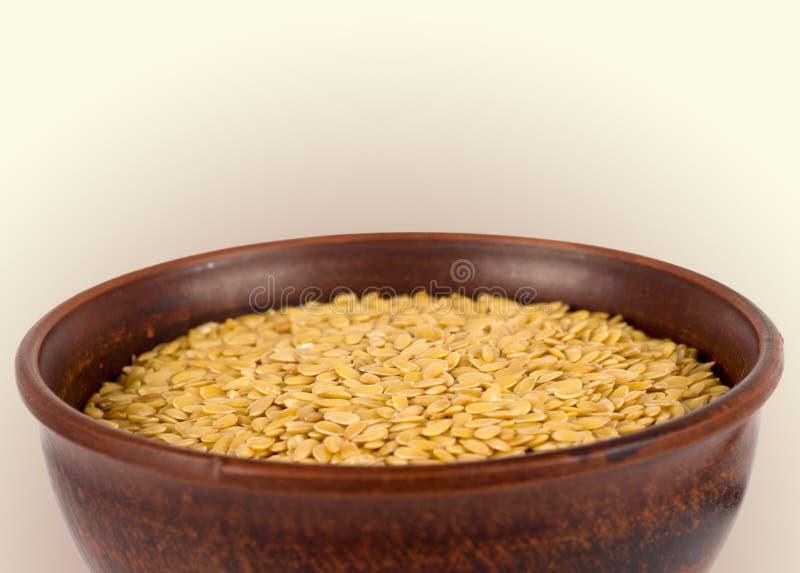 Seme di lino dorato in una ciotola di legno fotografia stock libera da diritti