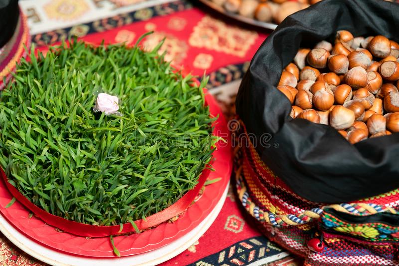 Semeni with a white rose in the middle and a bag of nuts on a tablecloth with national patterns and prints . royalty free stock photo