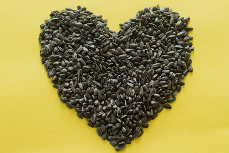 Semente de girassol orgânica na forma do coração No fundo amarelo Close up, vista superior fotos de stock