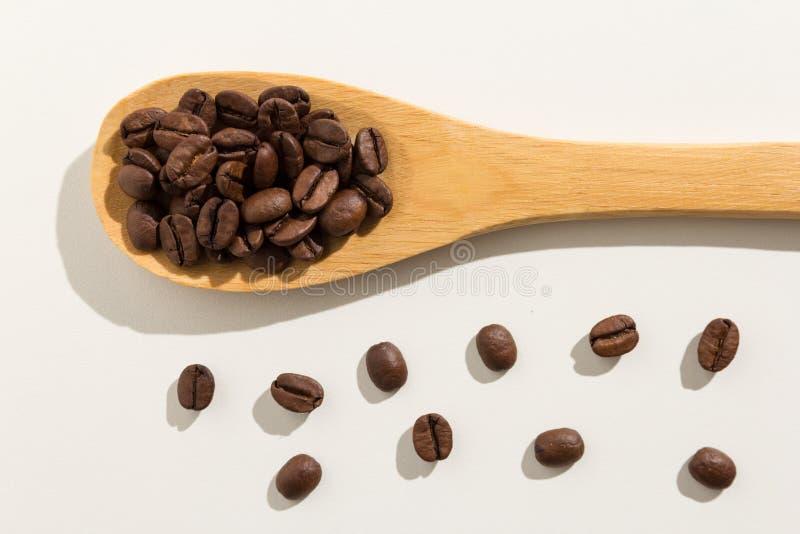Semente dos feijões de café Grões saudáveis em uma colher de madeira backg branco imagem de stock