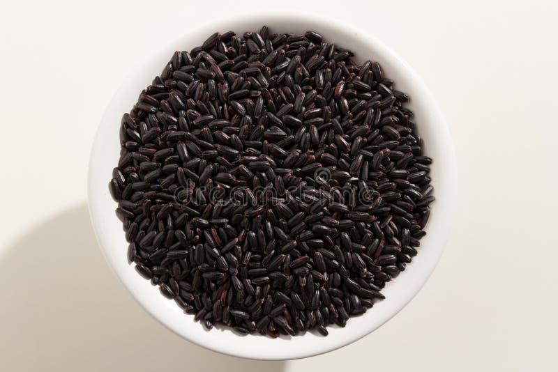 Semente preta do arroz Vista superior das grões em uma bacia Fundo branco fotos de stock royalty free