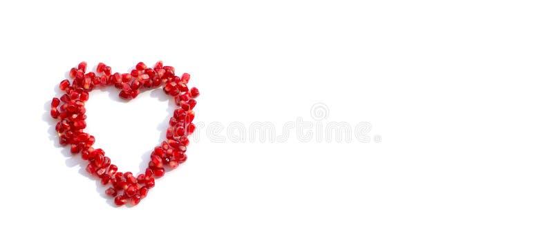 Sementes da romã dispersadas na forma de um coração fotos de stock royalty free