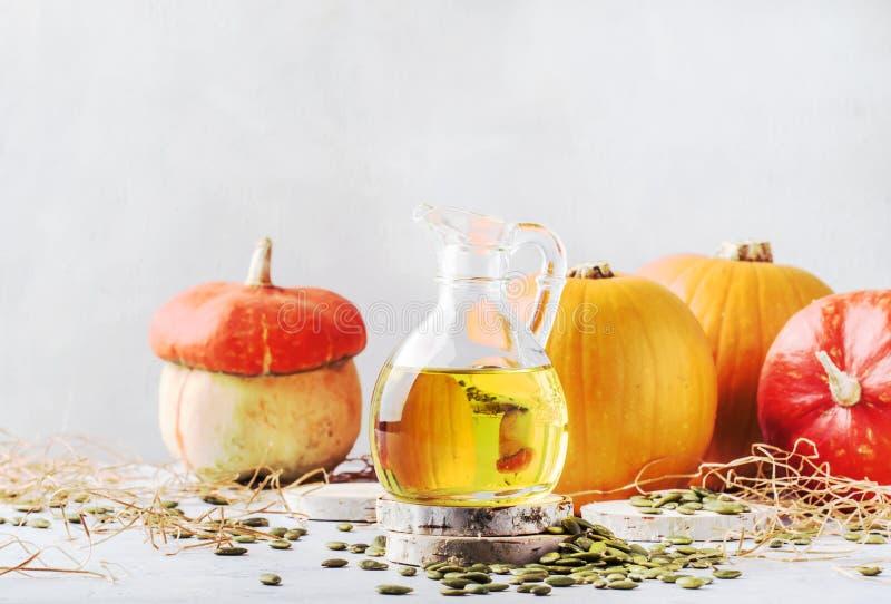 Sementes de abóbora claras do óleo no jarro de vidro no fundo rústico branco - cura e conceito saudável do alimento, foco seletiv imagem de stock