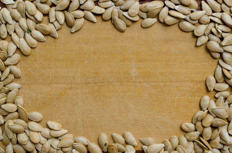 Sementes de ab?bora que formam uma ?rea fechado em uma superf?cie de madeira Quadro fotografia de stock