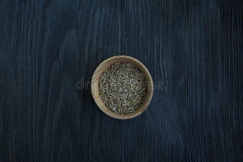 Sementes de cominhos em um prato de madeira Fundo de madeira escuro Vista de acima Close-up foto de stock royalty free