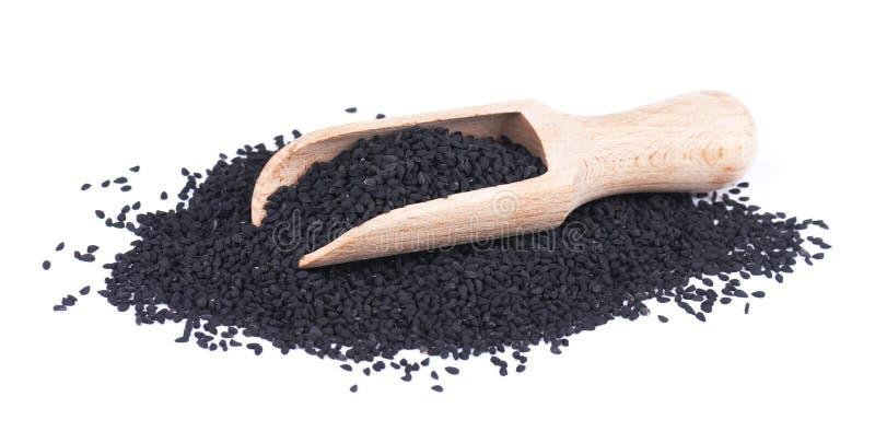 Sementes de cominhos pretas na colher de madeira, isolada no fundo branco Nigella sativa foto de stock