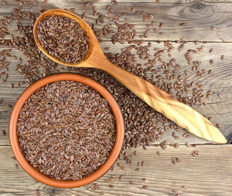 Sementes de linho na bacia com grões dispersadas em wi de madeira do fundo imagens de stock royalty free