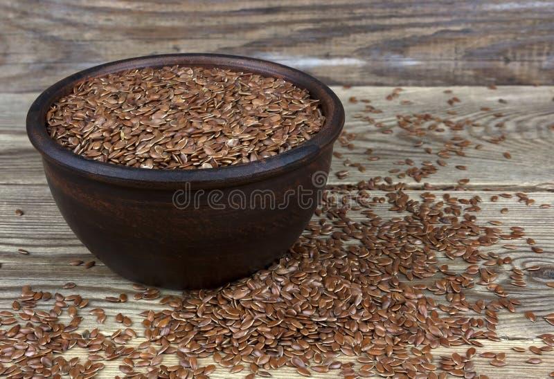 Sementes de linho na bacia com grões dispersadas no fundo de madeira imagem de stock royalty free