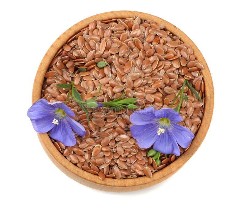 sementes de linho na bacia de madeira com a flor isolada no fundo branco flaxseed ou linhaça cereais Vista superior fotografia de stock royalty free