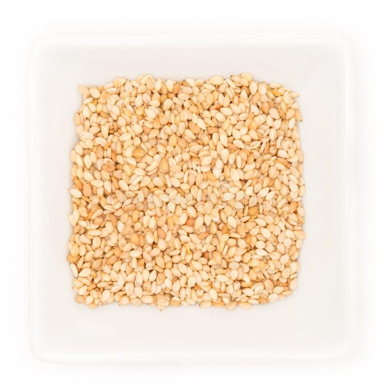 Sementes de sésamo ou grãos em uma bacia quadrada imagens de stock