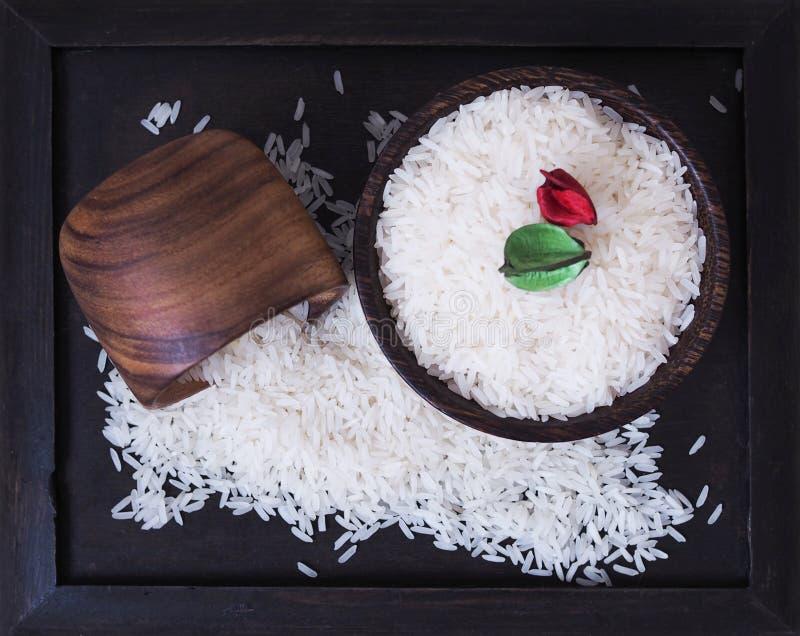 Sementes do arroz em um arroz de madeira preto da bandeja para cozinhar imagens de stock royalty free