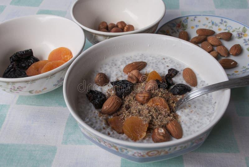 Sementes do chia do café da manhã, terra do linho, amêndoas, avelã, ameixa seca, abricó seco e iogurte foto de stock royalty free