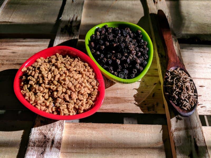 Sementes do feno-grego, da pimenta e de cominhos imagem de stock