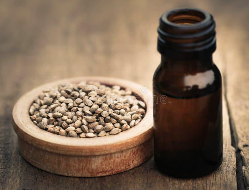 Sementes dos cannabis ou do cânhamo com óleo essencial na garrafa fotos de stock