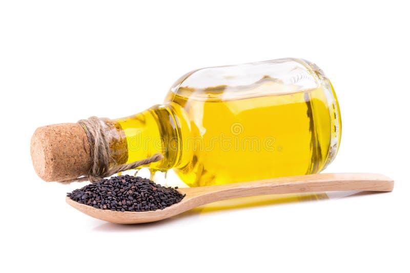Sementes e óleo de sésamo no fundo branco fotos de stock