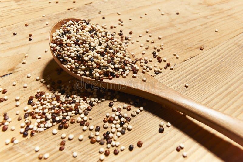 Sementes misturadas do quinoa na colher feita da madeira fotos de stock