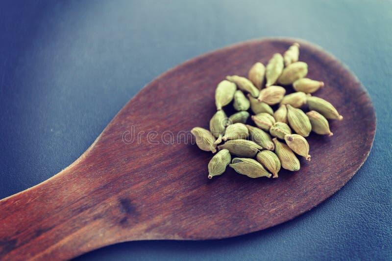 Sementes secas de cardamomo numa espátula de madeira castanha Especiarias e condimentos alimentares naturais Comida desagradável  foto de stock