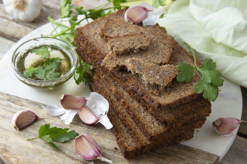 Sementes wholegrain cortadas, verdes, óleo e alho da sagacidade do pão na placa de corte carbohydrates foto de stock