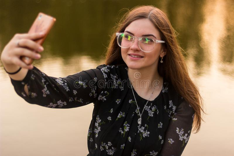 Semester och teknologi Färgrik stående av den nätta unga kvinnan som tar selfieståenden med hennes smartphone nära stranden royaltyfri bild