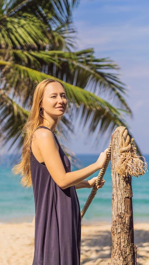 Semester på den tropiska ön Kvinna i hatt som tycker om havssikt från det VERTIKALA FORMATET för träbro för den Instagram mobilen arkivbild
