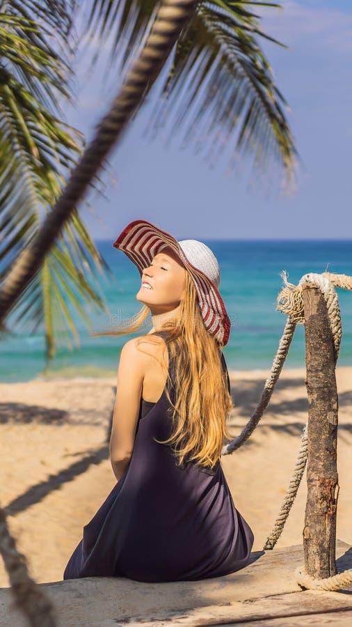 Semester på den tropiska ön Kvinna i hatt som tycker om havssikt från det VERTIKALA FORMATET för träbro för den Instagram mobilen royaltyfri bild
