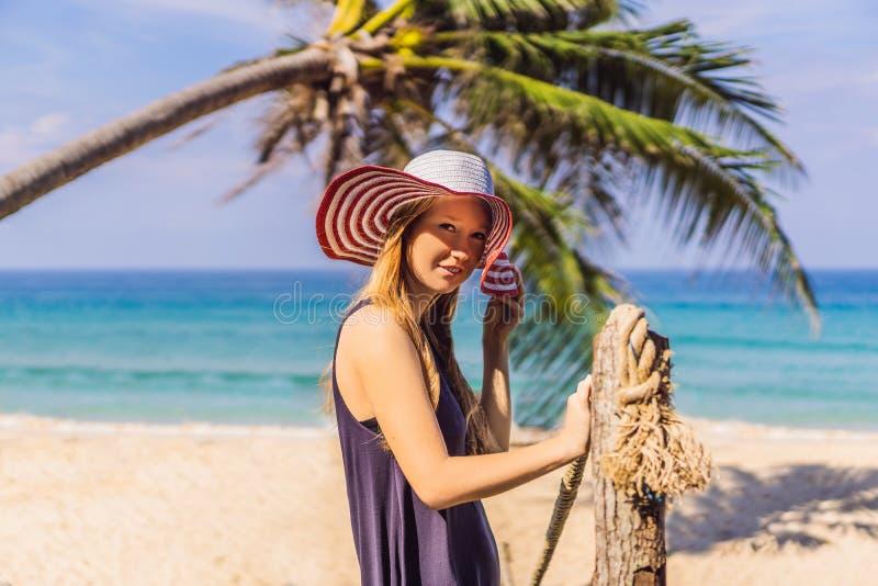 Semester på den tropiska ön Kvinna i hatt som tycker om havssikt från träbron royaltyfria foton