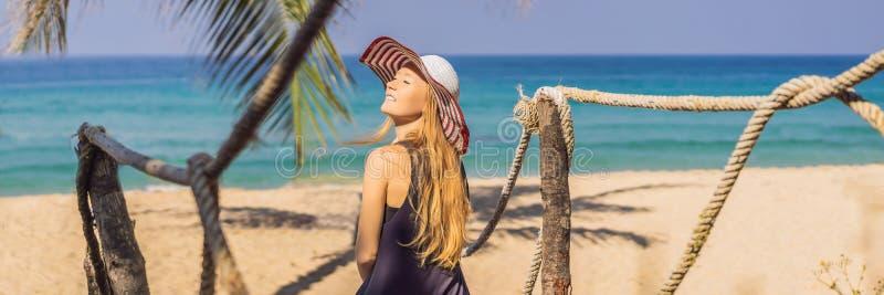 Semester på den tropiska ön Kvinna i hatt som tycker om havssikten från träbroBANER, LÅNGT FORMAT arkivbild