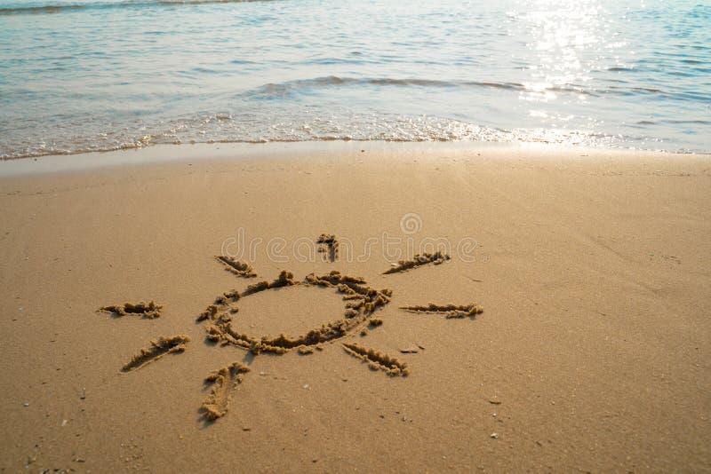 Semester p? sandstrandbegreppet The Sun symbol, solskenteckning in i sanden p? stranden p? Rayong, Thailand royaltyfri bild