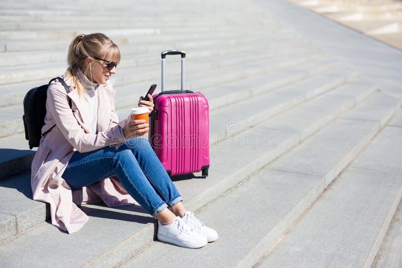 Semester-, turism- och loppbegrepp - turist för ung kvinna som sitter med smartphonen och resväskan royaltyfria foton