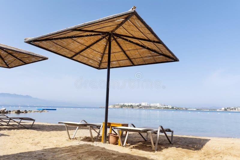Semesterbegrepp - strandparaplyer och sunbeds på en sandig strand arkivbild