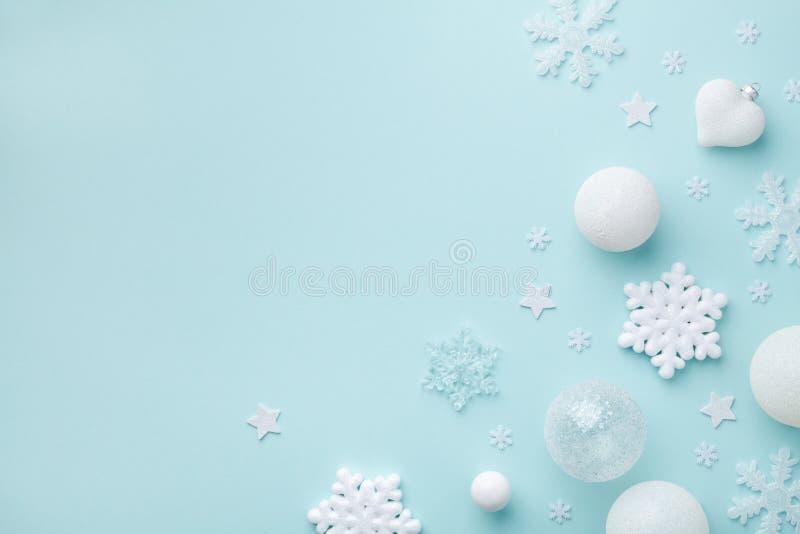 Semesterbollar och dekorativa snöflingor på bakgrunden till turkos-pastel Jul- eller nyårskort Minimalistiskt platt lägg royaltyfria foton