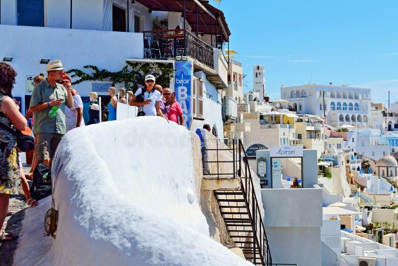 Semesterfirare som tycker om den Fira bySantorini ön Grekland arkivbilder