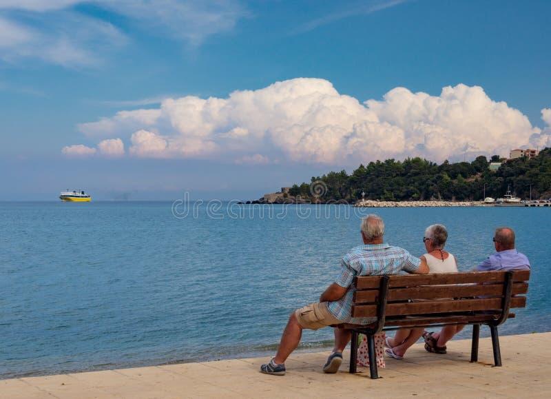 Semesterfirareturister på bänken på den högra turist- staden av den grekiska ön av Kefalonia i Grekland på kusten för Ionian hav  arkivfoto