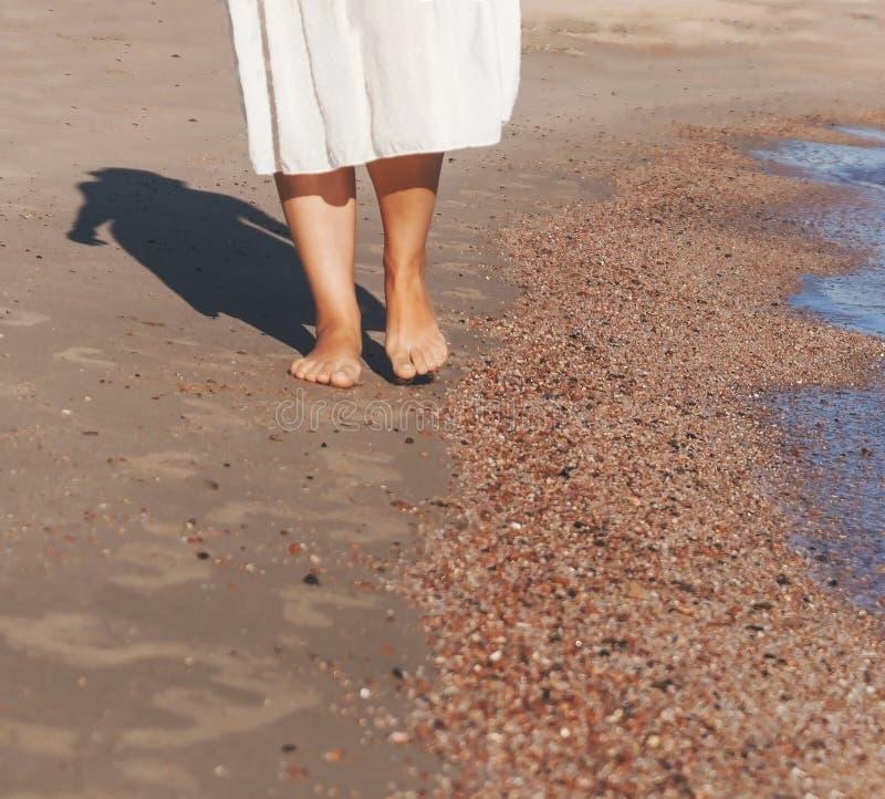 Semesterlopp - kvinnabencloseup som går på vit sand som kopplar av i strandkläder för strandtäckmantelpareo Sexiga och brunbrända royaltyfri foto