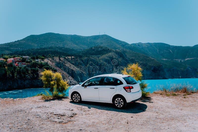 Semesterlopp med bilbegrepp Uthyrnings- hyrd bil framme av att förbluffa fjärden med turkosvatten Upptäck medelhavs- öar royaltyfria bilder