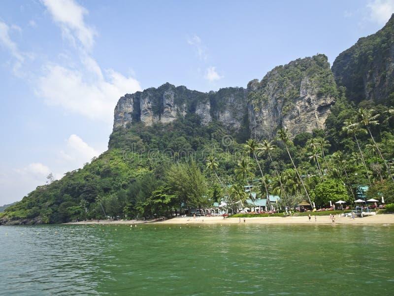 Semesterortbyn på stranden under berget med steniga branta klippor, palmträd, gul sand, azurt hav royaltyfri fotografi