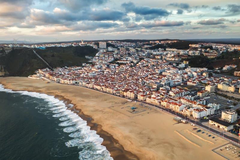 Semesterortstad vid havet eller havet med en ren strand utan folk, molnig sommar, Nazare av Portugal royaltyfri bild