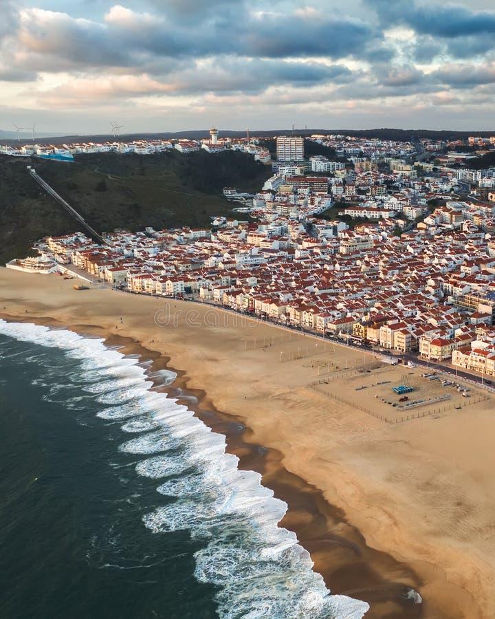 Semesterortstad vid havet eller havet med en ren strand utan folk, molnig sommar, Nazare Portugal royaltyfri bild