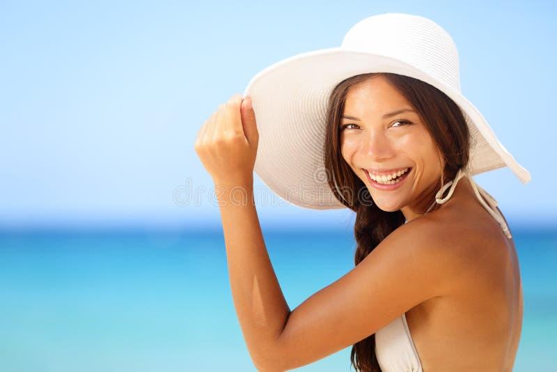 Semesterstrandkvinna som ler den lyckliga ståenden arkivbilder