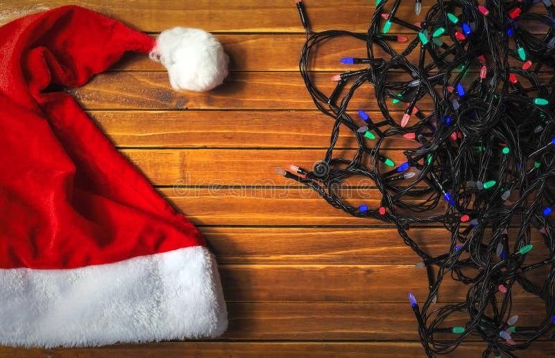 Semestra färgrika ljus av girlanden, den Santa Claus hatten fotografering för bildbyråer
