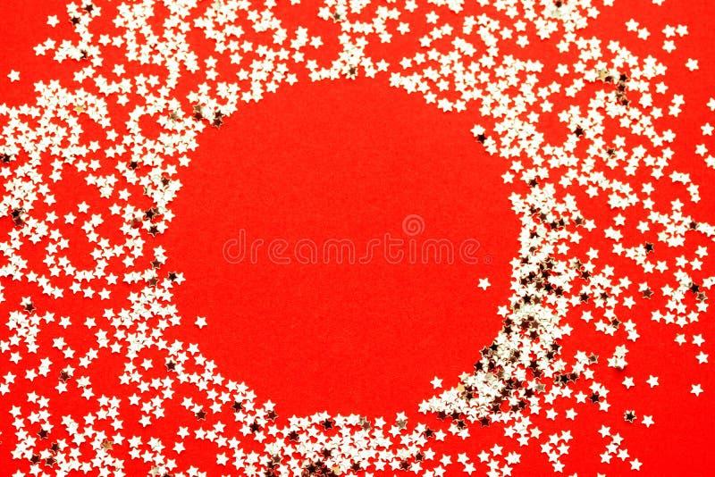 Semestra festligt blänker bakgrund Stjärnamodell som ordnas i cirkelkrans på den ljusa röda karmosinröda bakgrunden Nya år jul royaltyfri bild