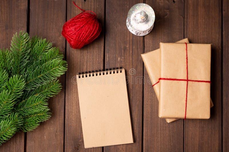 Semestra flatlay, gåvor som slås in med hantverkpapper, anteckningsboken med tomt papper och gran på en lantlig mörk trätabell av royaltyfri foto