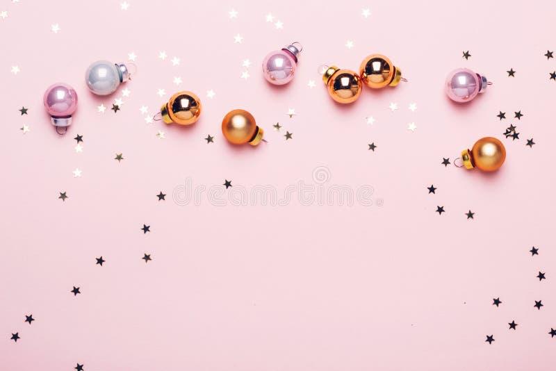 Semestra rosa bakgrund för jul med guld- skinande bollar och konfettier arkivbilder