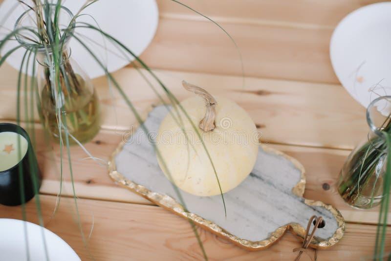 Semestra tabellgarnering med vita dekorativa pumpor, vita plattor och stearinljus p? tr?bakgrund Lekmanna- l?genhet, b?sta sikt arkivbild