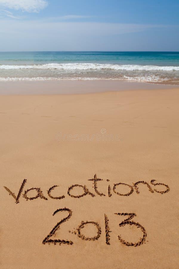 Semestrar 2013 som är skriftliga i sand på tropisk strand arkivfoto