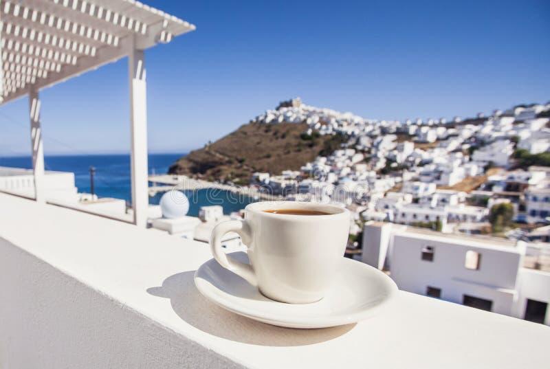 Semestrar i Grekland Traditionellt grekiskt kaffe på en balkong med den härliga grekiska medelhavs- staden på bakgrunden arkivfoto