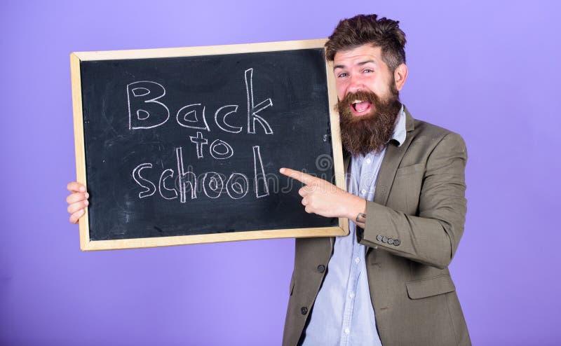 Semestre novo na escola Continue sua educação connosco O homem farpado do professor está e guarda o quadro-negro com fotografia de stock royalty free