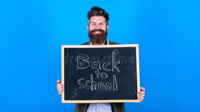 Semestre novo na escola O homem farpado do professor está e guarda o quadro-negro com inscrição de volta ao fundo do azul da esco imagens de stock royalty free