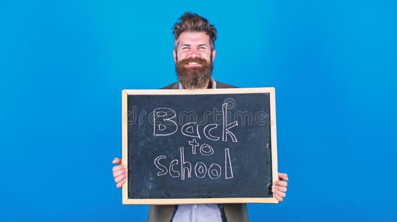Semestre novo na escola O homem farpado do professor est? e guarda o quadro-negro com inscri??o de volta ao fundo do azul da esco fotografia de stock royalty free